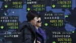 Women walk past an electronic stock board of a securities firm in Tokyo on March 27, 2015. (AP / Eugene Hoshiko)