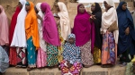 A tired Nigerian woman sits down to rest as others queue, while they face long delays to cast their vote in the afternoon at a polling station in Daura, the home town of opposition candidate Gen. Muhammadu Buhari, in northern Nigeria Saturday, March 28, 2015. (AP / Ben Curtis)