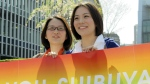 "Koyuki Higashi, right, and Hiroko Masuhara, a rare visible and vocal lesbian couple in Japan, smile with a rainbow banner reading: ""Thank you, Shibuya"" in front of Shibuya ward office in Tokyo after Shibuya ward became the first locale in Japan to recognize same sex partnerships as the equivalent of a marriage on March 31, 2015. (AP / Yuri Kageyama)"