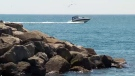 A boat zooms past the Lake Ontario shoreline on Wednesday, May 13, 2015.