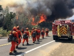Fire crews walk on U.S. Highway 20 as a fire approaches near Clearlake, Calif., Monday, Aug. 3, 2015. (AP / Terry Chea)