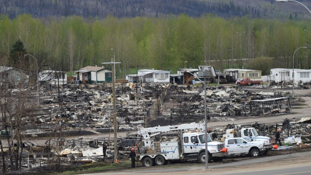 Electrical crews are see working among burned-out buildings in the Beacon Hill neighbourhood of Fort McMurray, Alta., during a media tour of the fire-damaged Alberta city on Monday, May 9, 2016. (THE CANADIAN PRESS/Ryan Remiorz)