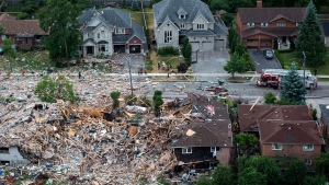 Firefighters examine debris after a house explosion in Mississauga, Ont., Tuesday, June 28, 2016 (Eduardo Lima / THE CANADIAN PRESS)