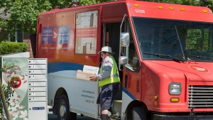 A Canada Post employee fills a community mail box in Dartmouth, N.S. on Thursday, June 30, 2016. (Andrew Vaughan / THE CANADIAN PRESS)
