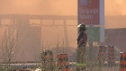 A firefighter watches through the smoke as fire consumes a Hyde Park plaza in London, Ont, on Thursday, June 30, 2016. (Marek Sutherland / CTV London)