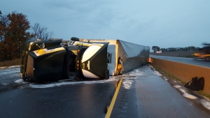 A transport truck flipped over, spilling about 450 gallons of diesel fuel onto the Highway 401 west of Woodstock, Ont., on Thursday, Oct.20, 2016. (CTV London)