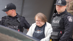 Elizabeth Tracey Mae Wettlaufer is led out of court by Toronto police officers on Oct. 25, 2016. (Geoff Robins/The Globe and Mail)