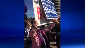 """A pro-Mike Bradley protester holds a campaign sign up to Sarnia Coun. Cindy Scholten's sign that states, """"Say No To Bullying"""" during a rally on Oct. 28, 2016. (Bryan Bicknell/CTV)"""